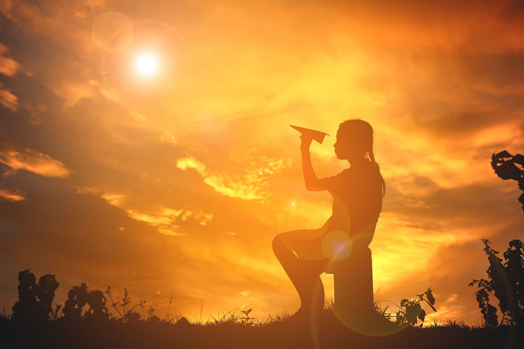 Silhouette girl playing with paper airplane while sitting on tree stump during sunset