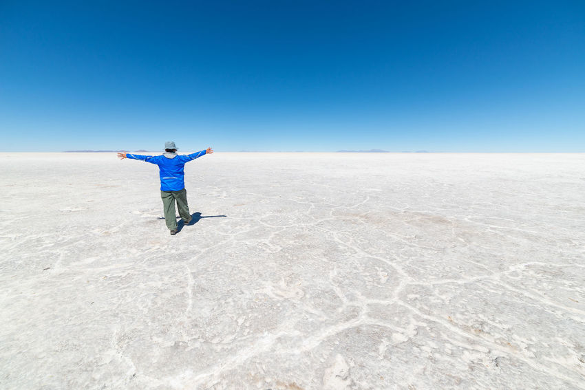 Tourists exploring the world famous Uyuni Salt Flat, among the most important travel destination in the Bolivian Andes. Wide angle view, clear blue sky. Adult Adults Only Arid Climate Beauty In Nature Blue Clear Sky Day Desert Full Length Landscape Men Nature One Man Only One Person Outdoors People Real People Salt - Mineral Salt Basin Salt Flat Scenics Sky Standing Young Adult