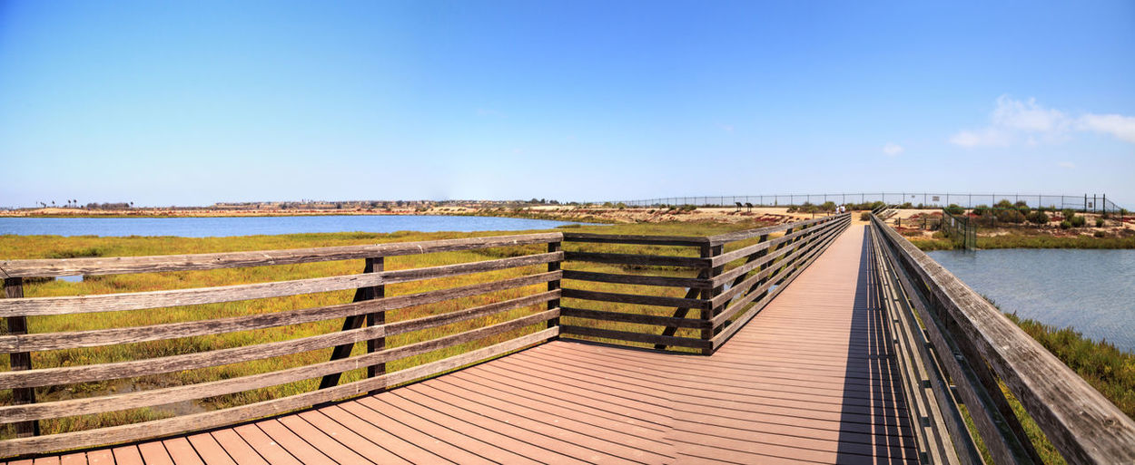 Bridge along the peaceful and tranquil marsh of Bolsa Chica wetlands in Huntington Beach, California, USA Bolsa Chica Bolsa Chica Nature Preserve California Huntington Beach Marsh Path Travel Bolsa Chica Wetlands Bridge Day Foot Bridge Foot Bridge Over Water Journey Nature No People Orange County Outdoors Scenics Sky