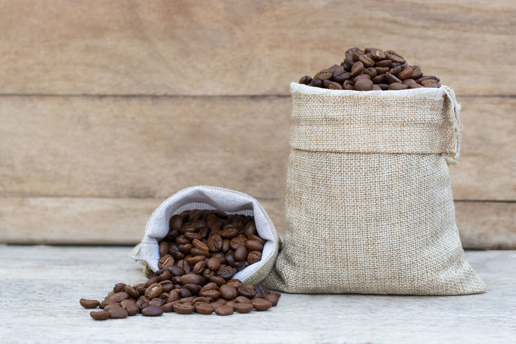 Beans Coffee Abundance Bag Brown Burlap Caffeine Coffee Coffee - Drink Container Food Food And Drink Freshness Heap Indoors  Jute Large Group Of Objects No People Roasted Coffee Bean Sack Still Life Table Wellbeing