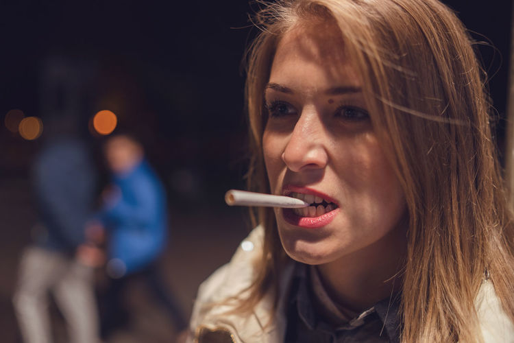 Close-up of woman biting cigarette while standing outdoors