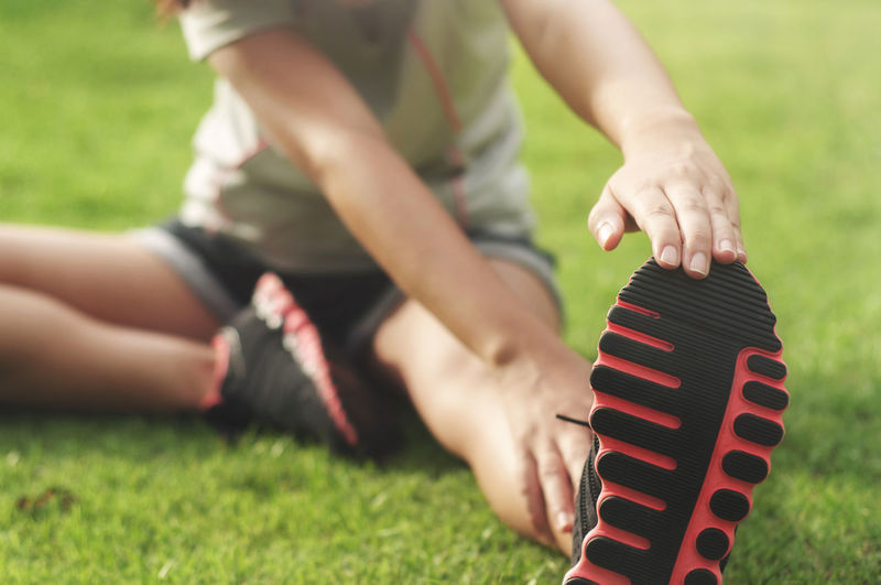 Low Section Of Woman Exercising While Sitting On Field