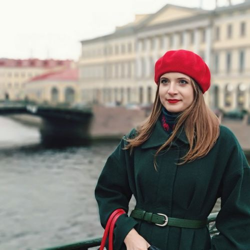 Young woman wearing warm clothing while looking away in city by canal