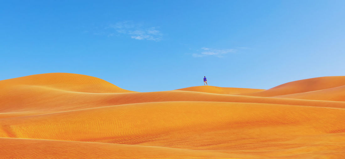 Mid distance view of man standing at desert against blue sky