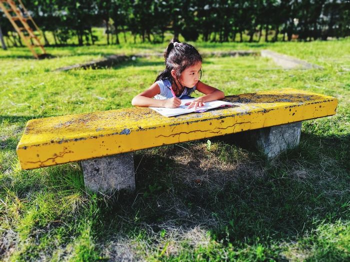 Girl writing in book at bench