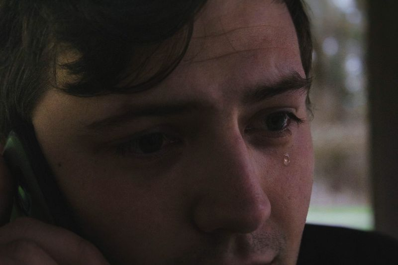 Close-up portrait of crying man on phone