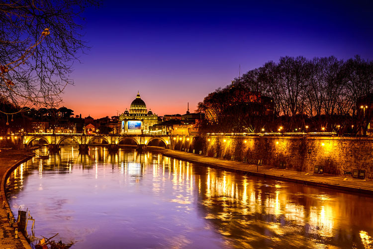 River And Illuminated St Peter Basilica Against Sky At Dusk