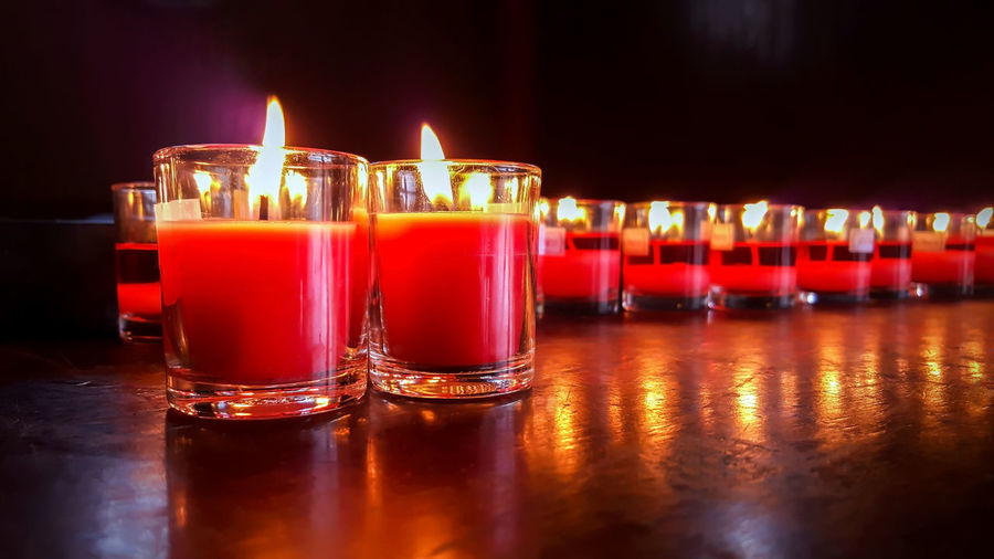 Many candle flames glowing in the dark. Alcohol Bar - Drink Establishment Bar Counter Burning Candle Close-up Dark Drink Fire Food And Drink Glass Group Of Objects Illuminated In A Row Indoors  Luxury Nightlife No People Red Reflection Refreshment Table