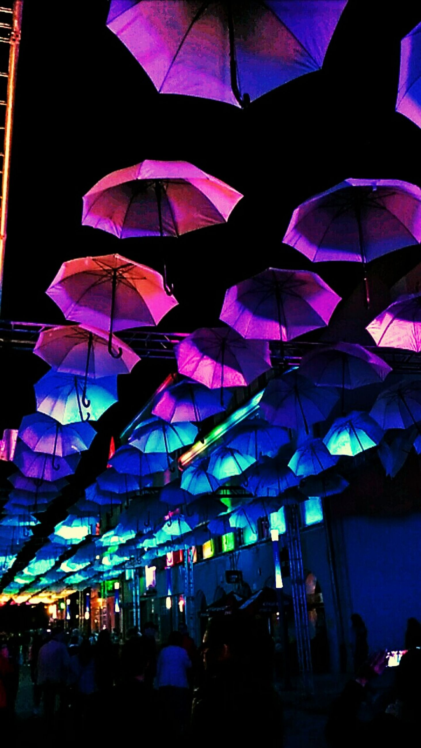 umbrella, multi colored, illuminated, low angle view, creativity, outdoors, city life, vibrant color, tourism, sky, architectural feature, pink color, colorful, majestic, modern