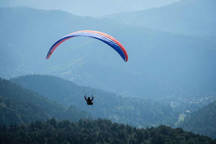 Adventure Beauty In Nature Exhilaration Extreme Sports Flying Freedom Joy Leisure Activity Lifestyles Mid-air Mountain Mountain Range One Person Outdoors Parachute Paragliding Real People Scenics - Nature Sport Tranquil Scene Transportation Unrecognizable Person