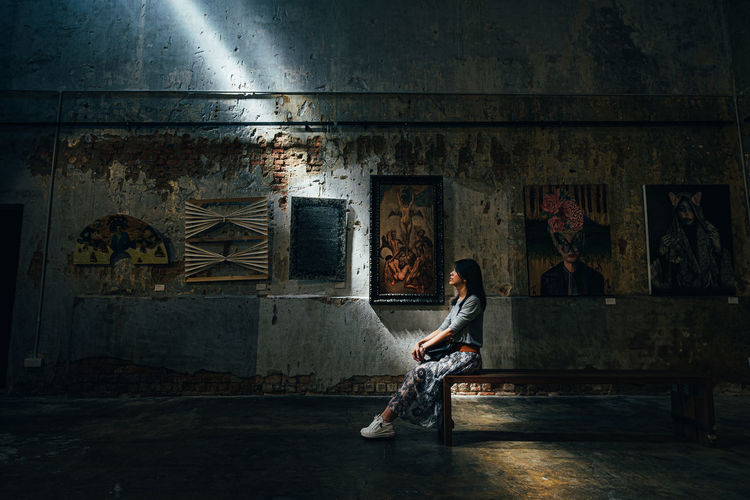 Woman sitting on abandoned building