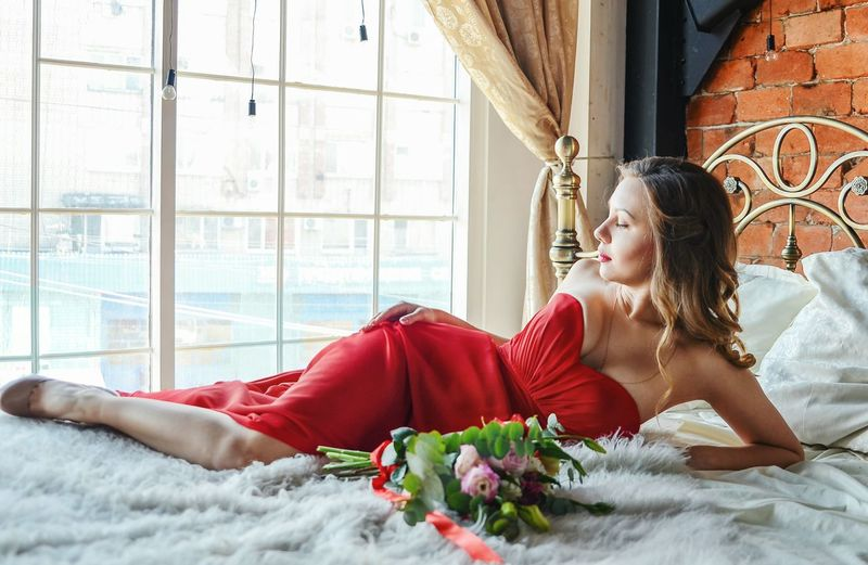 Beautiful Young Woman With Eyes Closed By Bouquet Lying On Bed At Home
