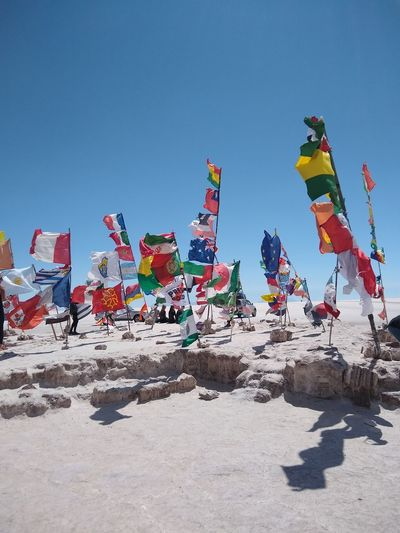 Flags In The Wind  Salt Flats Of Uyuni Clear Sky Sunlight Sky Colorful