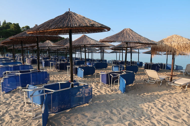 Sunshade on a beach Beach Life Deck Chair Relaxing Sunny Travel Beach Cafe Nature No People Nobody Outdoors Parasol Protection Sand Scenics - Nature Shade Sky Summer Sunshade Thatched Roof Tourism Tranquility Umbrella Vacation Water