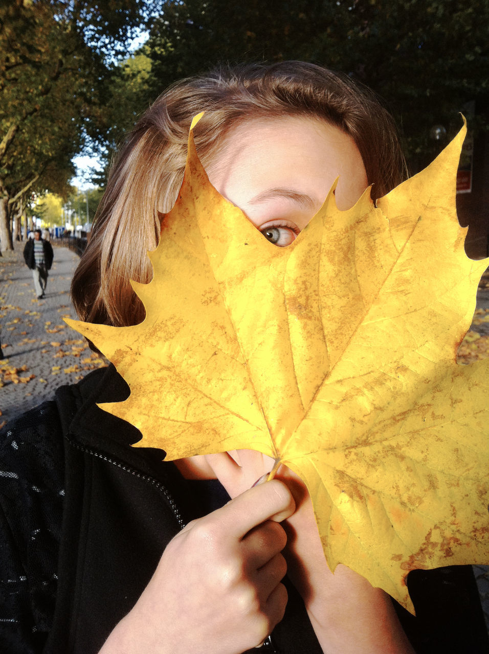 CROPPED IMAGE OF WOMAN WITH YELLOW LEAVES