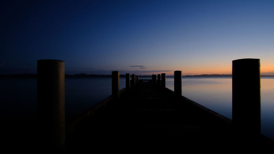 """""""Way to tranquility"""" Auckland Breaking Morning New Zealand Scenery Scenic Beauty In Nature Clear Sky Dawn Horizon Over Water Leading Maraetai Nature New Zealand No People Outdoors Scenics Sea Silhouette Sky The Way Forward Tranquility Water"""