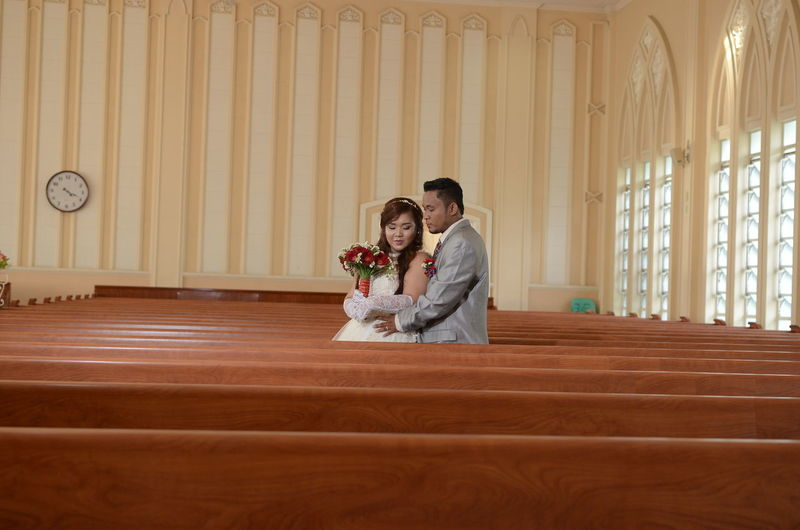 Bride and groom standing amidst benches in church