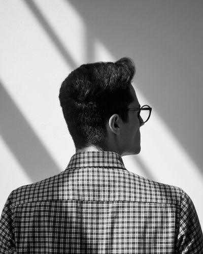 Rear view of man looking away against wall