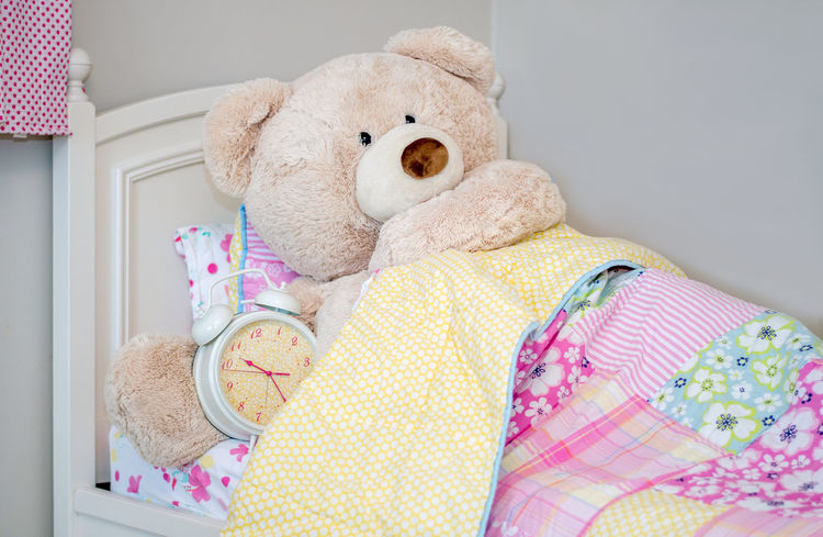 This giant teddy bear is making sure he wakes up on time, by taking a big alarm clock to bed with him Fun Pink Alarm Clock Animal Representation Bed Bedroom Childhood Close-up Day Domestic Room Furniture Home Interior Indoors  Innocence Life Size  Pillow Pink Color Representation Softness Still Life Stuffed Toy Teddy Bear Toy Toy Animal Yellow