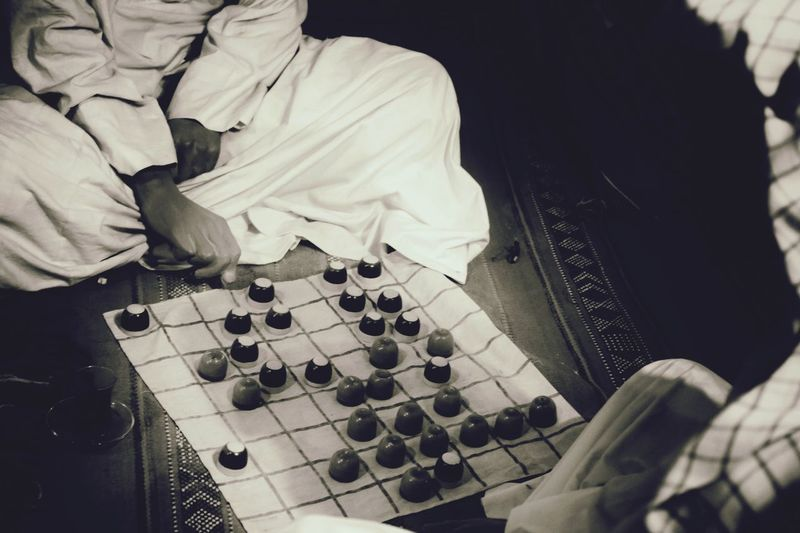 Low Section Of Man Playing Checkers