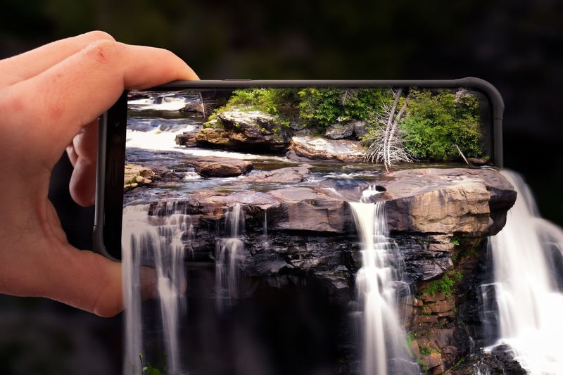 Digital composite image of waterfall in mobile phone being held by person