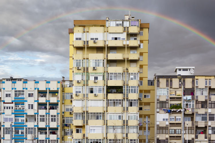 Low angle view of residential buildings against rainbow in sky
