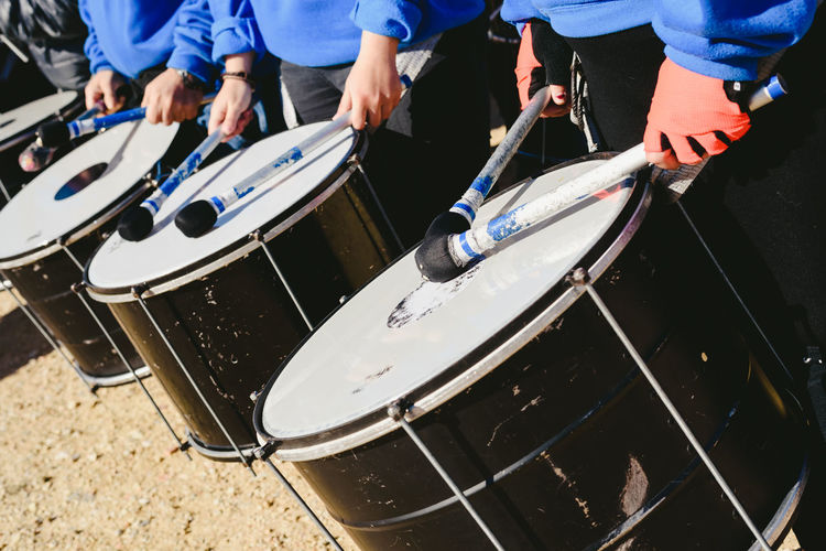 Midsection of men playing drums while standing outdoors
