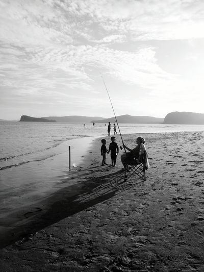 Children looking at woman fishing on beach