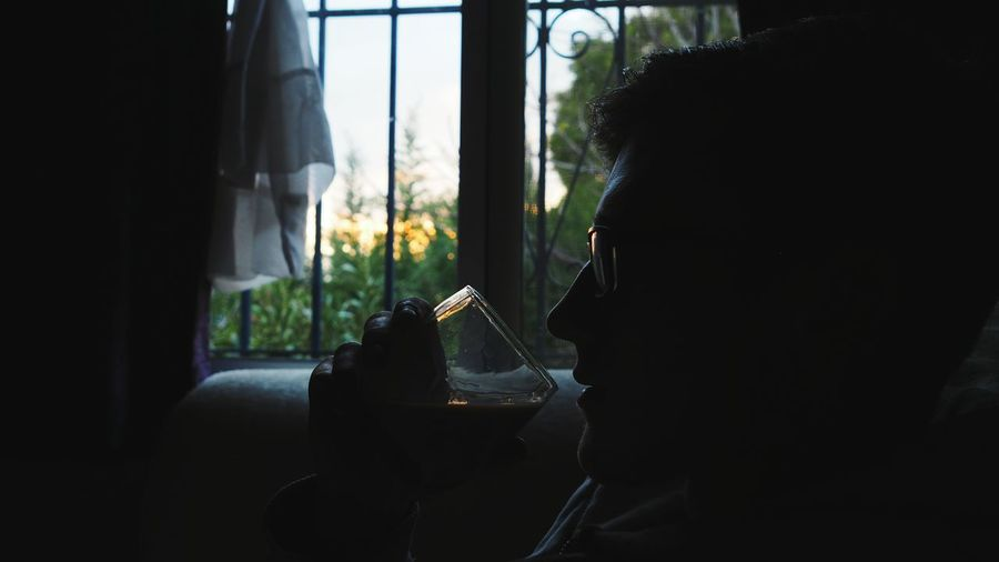 Close-Up Of Man Having Wine By Window At Home