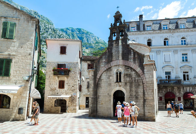 Tourists entering a small church in Kotor, Montenegro in June, 2017 Architecture Balkan Church Kotor Bay Tourist Tourist Attraction  Tranquility Travel UNESCO World Heritage Site Vacations Architecture Building Exterior Built Structure Culture History Kotor Kotor, Montenegro Men Montenegro Mountain Real People Tourism Travel Destinations Women Yacht Charter Destination