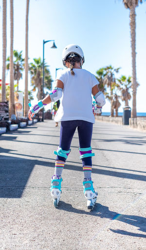 Rear view of girl inline skating on road