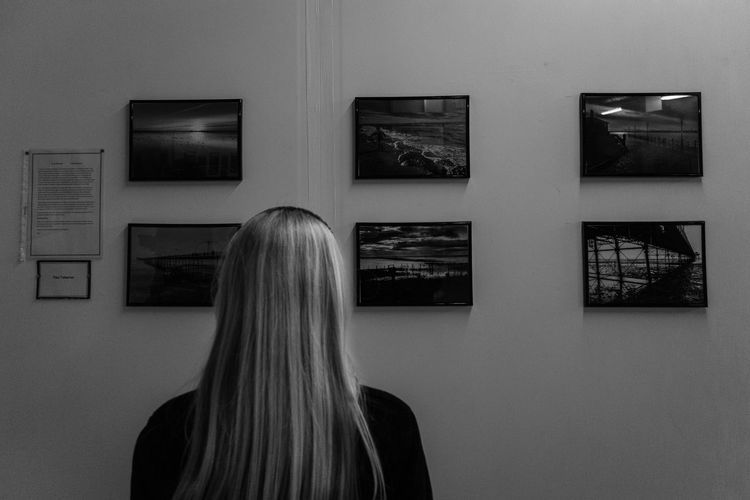 Rear View Of Blond Woman Looking At Picture Frames Mounted On Wall