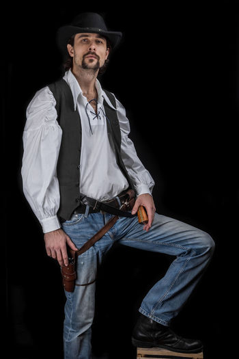 Handsome young man. This is an American cowboy. A vow to a white shirt, brown waistcoat and blue jeans. Black shoes on the feet. Carries a shtyapa, on a belt two pistols. The hair is of medium length; on the face is a beard and mustache. Authentic photo. Culture of America. Cowboy Wild West America American Gun National Authentic Moments Lifestyles Lifestyle One Person Candid Authentic Hat Three Quarter Length Front View Black Background Clothing Adult Young Adult Standing Portrait Looking At Camera Confidence  Jeans Men