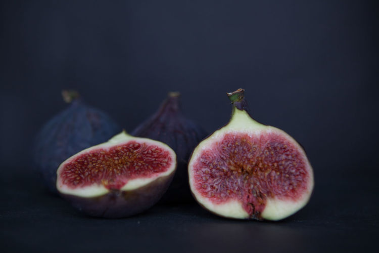 Beautiful fresh blue violet figs on dark stone background with empty copyspace close up vie from above. Fruit Food And Drink Healthy Eating Freshness Wellbeing Food Fig Studio Shot Indoors  Still Life No People Close-up Black Background Cross Section SLICE Group Of Objects Three Objects Ripe Colored Background
