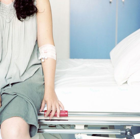 Midsection of mid adult woman sitting on bed at hospital