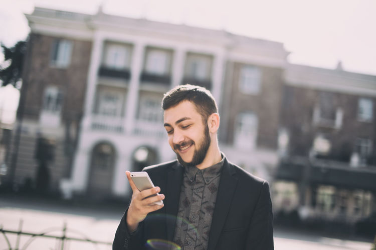 Wireless Technology Young Adult Architecture One Person Mobile Phone City Smart Phone Young Men Technology Communication Building Exterior Portable Information Device Built Structure Connection Front View Smiling Portrait Lifestyles Standing Outdoors