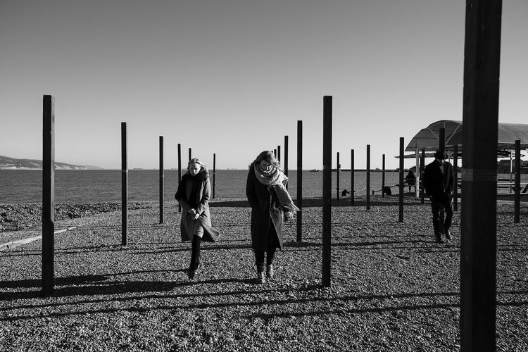 A group of young people on the beach. Two girls and a guy in a coat and hat go somewhere. Wooden piles create an interesting perspective in the frame. The sea coast is strewn with round stones, the water is calm, the sky is clear, without clouds. People are warmly dressed, it's a sunny winter day. Lifestyles Lifestyle Authentic Moments Authentic Candid Real People Blackandwhite Black And White Sky Nature Clear Sky Group Of People Water Men Land Sea Leisure Activity Adult People Standing Women Day Outdoors Full Length Perspective