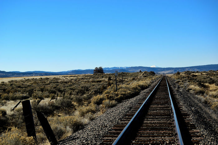 View down railroad tracks with mountains off in the distance. California Copy Space D Modoc County USA Alturas Blue Blue Sky Clear Sky Day Landscape Mountain Nature No Clouds No People No People, Outdoors Rail Transportation Railroad Track Scenics Sky The Way Forward Transportation