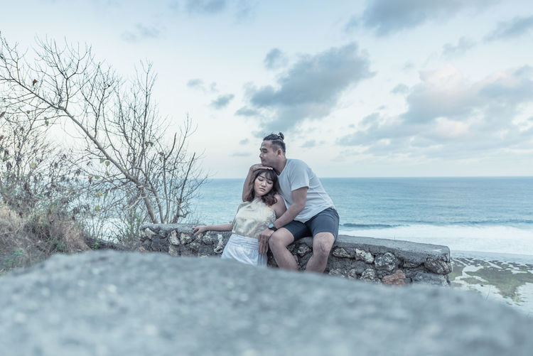 Couple embracing while sitting against sea and sky