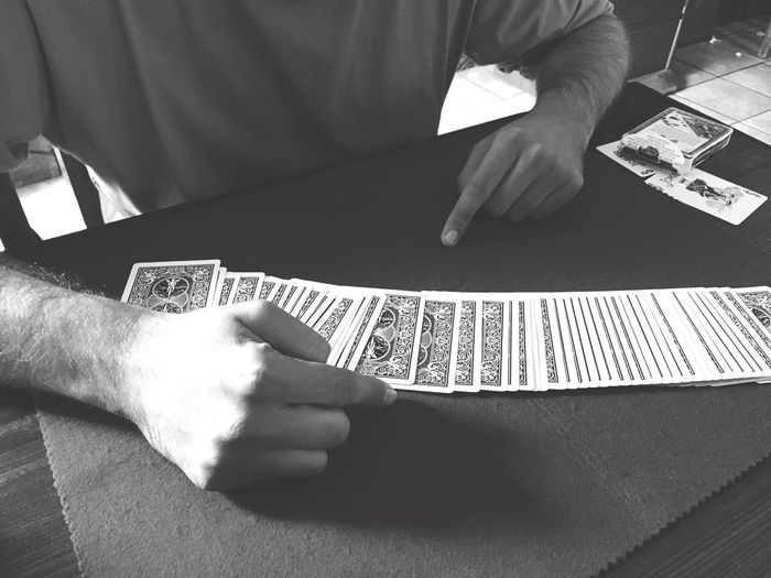 Cropped Image Of Magician With Cards At Table