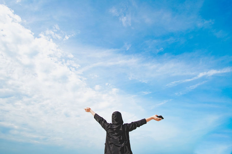 Low Angle View Of Person With Arms Outstretched Standing Against Blue Sky