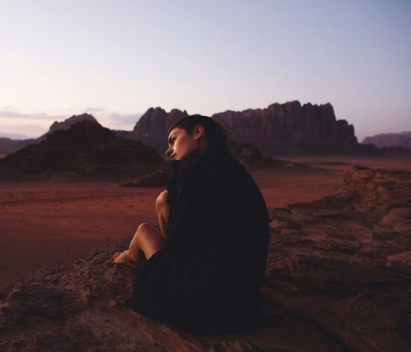 Wadi Rum, Jordan, Middle East Real People Rock - Object Sitting One Person Mountain Young Women Young Adult Nature Landscape Sky Lifestyles Desert Leisure Activity Clear Sky Full Length Outdoors Beauty In Nature Scenics Day People Wadi Rum Jordan Middle East Serenity Fresh On Market 2017