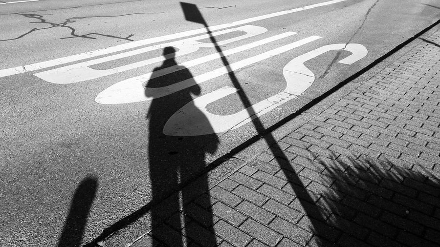Waiting for the Bus.. 🚌 Shadow Focus On Shadow Silhouette Transportation Bus Stop Public Transportation Outdoors Standing Morning Light Morning Rituals Bnw Streetphotography Streetphotography_bw Road Road Marking Street Long Shadow - Shadow
