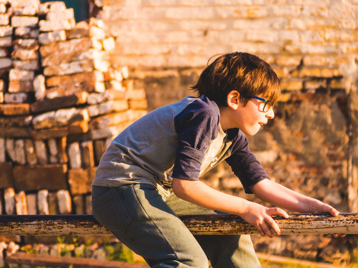 Side view of boy sitting on railing against brick wall