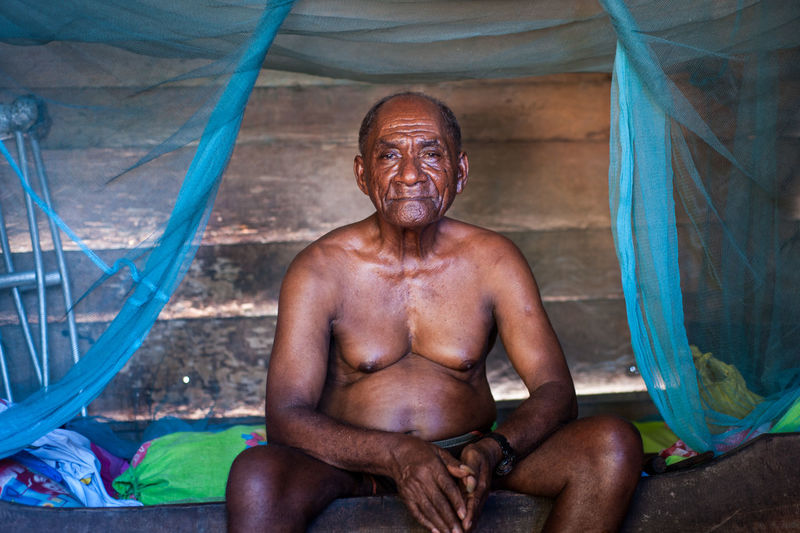 Papua Fisherman, Indonesia. Adult Front View Happiness Indoors  Lifestyles Looking At Camera Males  Mature Adult Mature Men Men Muscular Build One Person Portrait Real People Shirtless Sitting The Potraitist - 2018 EyeEm Awards Three Quarter Length
