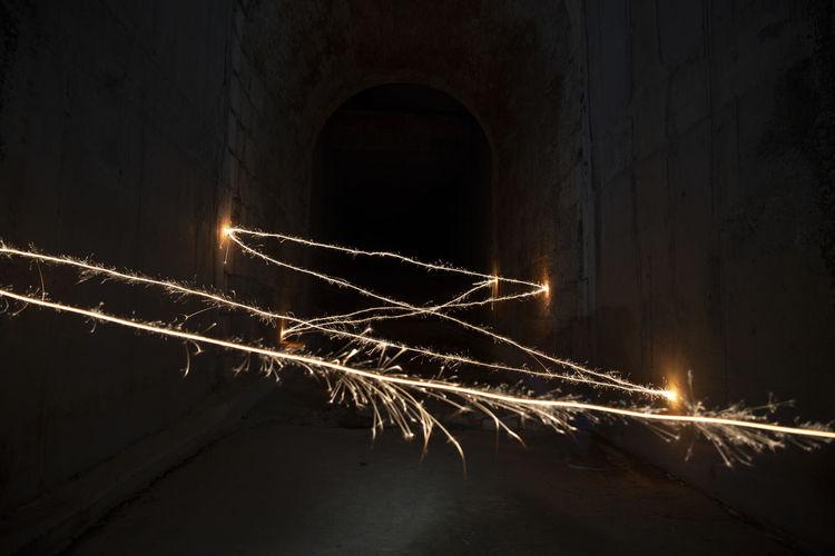Light trails in illuminated tunnel at night