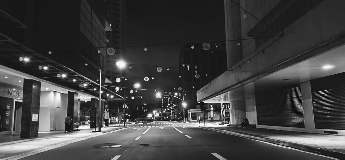 Empty road amidst illuminated buildings in city at night