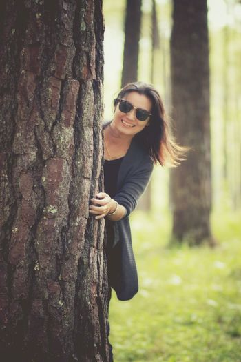Portrait of smiling young woman holding tree trunk