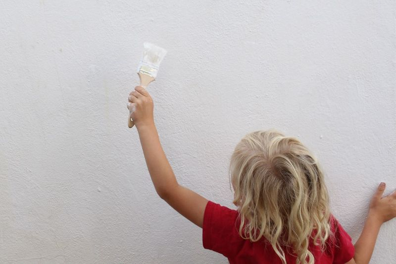 Rear view of girl painting while standing against wall