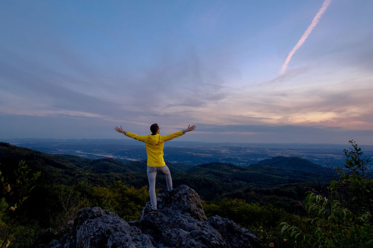 A man stands on cliffs, in front of a big landscape. Adventure Arms Outstretched Arms Raised Beauty In Nature Cloud - Sky Freedom Human Arm Leisure Activity Looking At View Mountain Mountain Range Non-urban Scene One Person Outdoors Real People Rear View Rock - Object Scenics Scenics - Nature Sky Standing Tranquil Scene Tranquility Vacations Be Brave Moments Of Happiness 2018 In One Photograph Stay Out